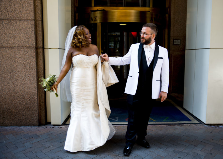 bride and groom in white suit jacket in front of the Andaz