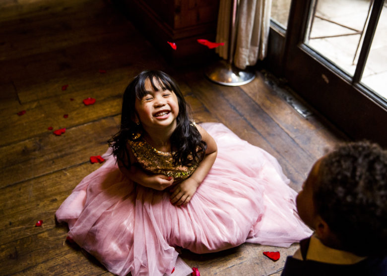 little girl in pink tutu sitting on the floor laughing