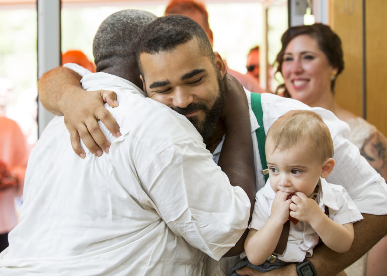 groom embracing older man with one hand and holding baby with the other