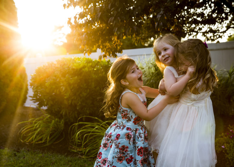 three little girls playing in a yard with a sun flare behind them
