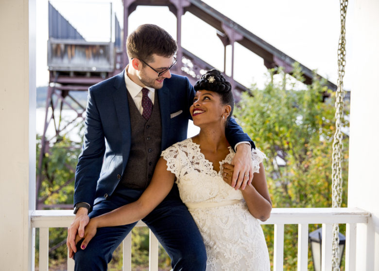 groom sitting on a porch railing with arm around bride looking up at him