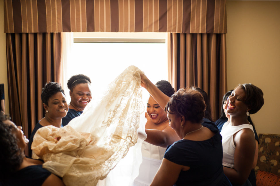 bride surrounded by bridesmaids helping her into dress