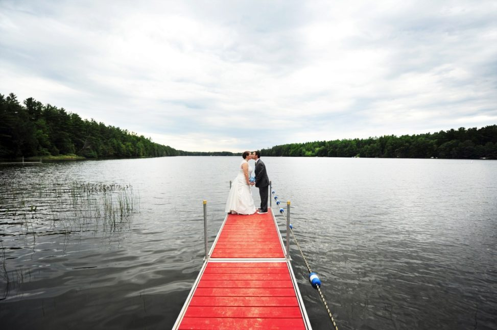 couple standing on the edge of a dock kissing