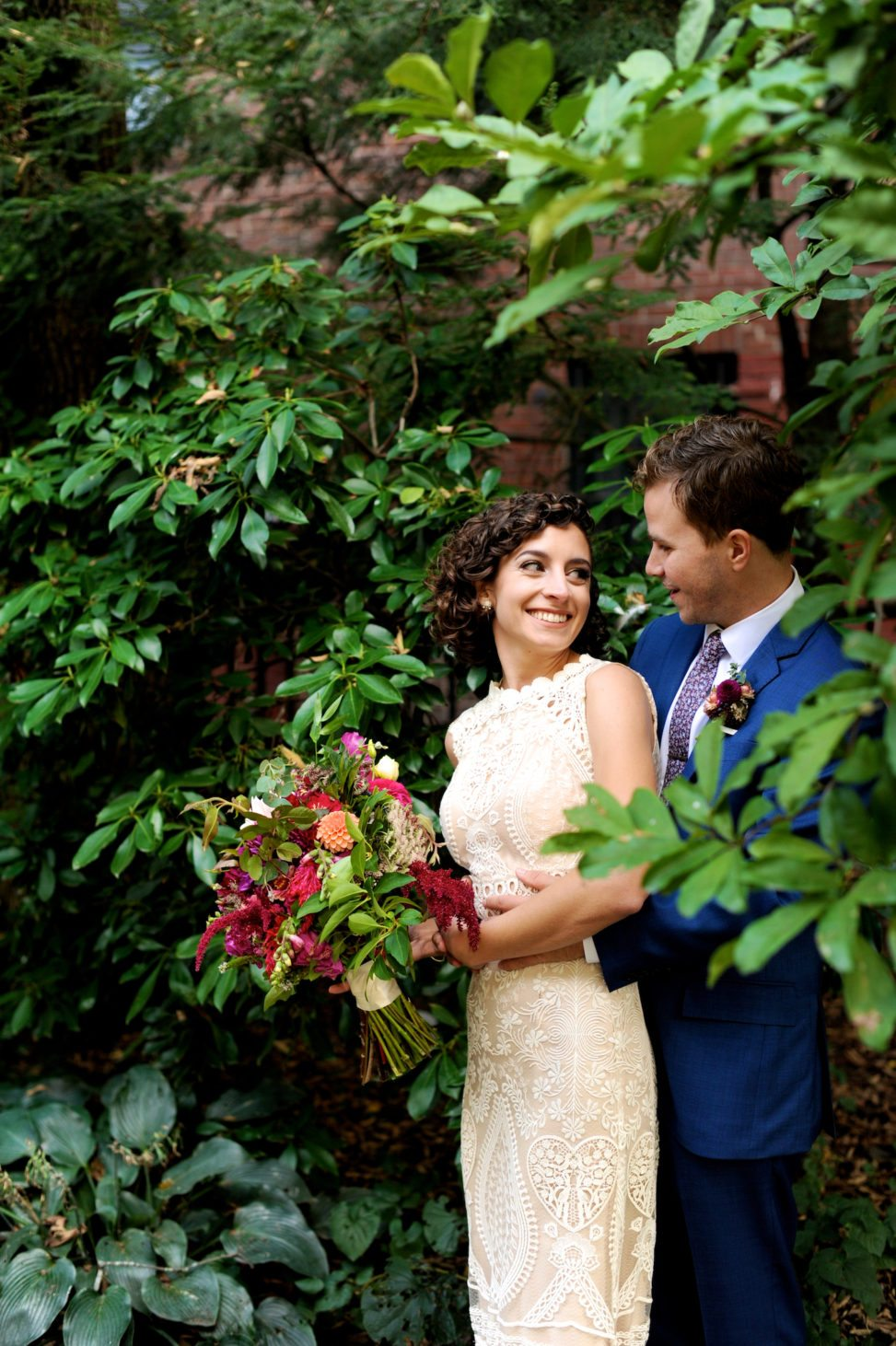 portrait of bride and groom surrounded by greenery