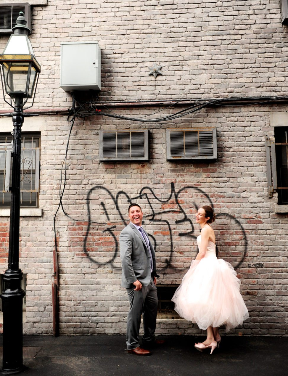 a bride and groom pose in front of graffiti