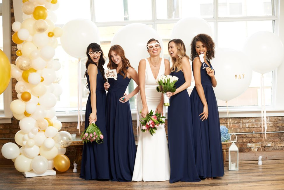 bride in white holding pink and green bouquet surrounded by bridesmaids in floor-length navy dresses, some wear silly glasses, others hold props for the photo