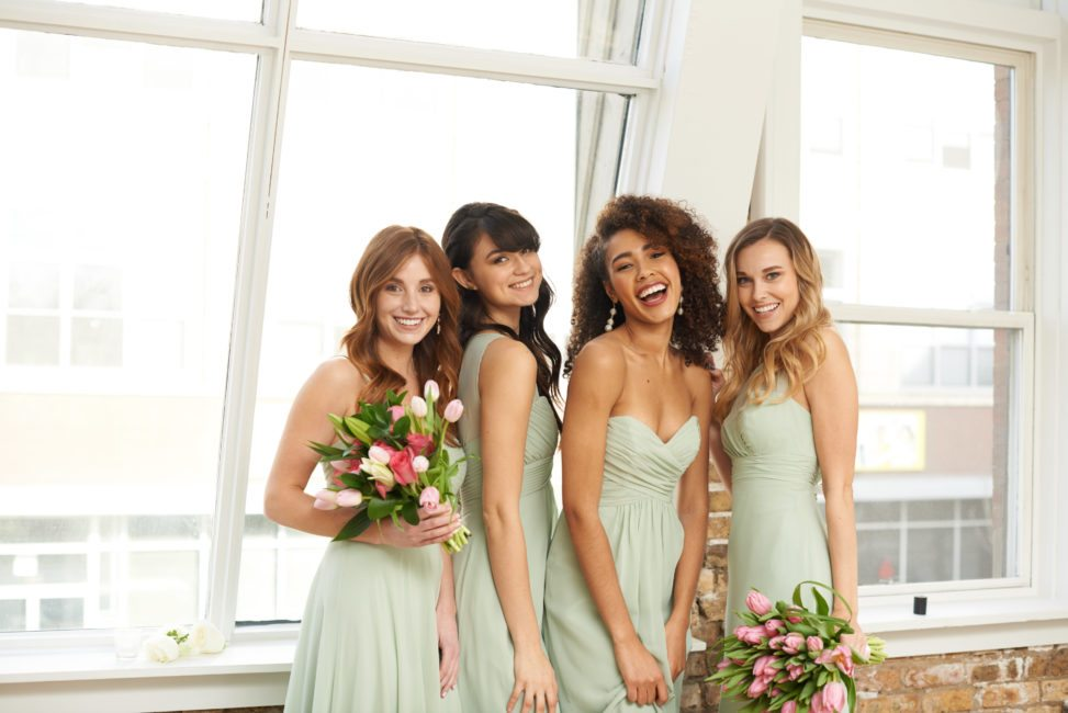 bridesmaids smiling in front of loft windows wearing light mint green dresses in different styles