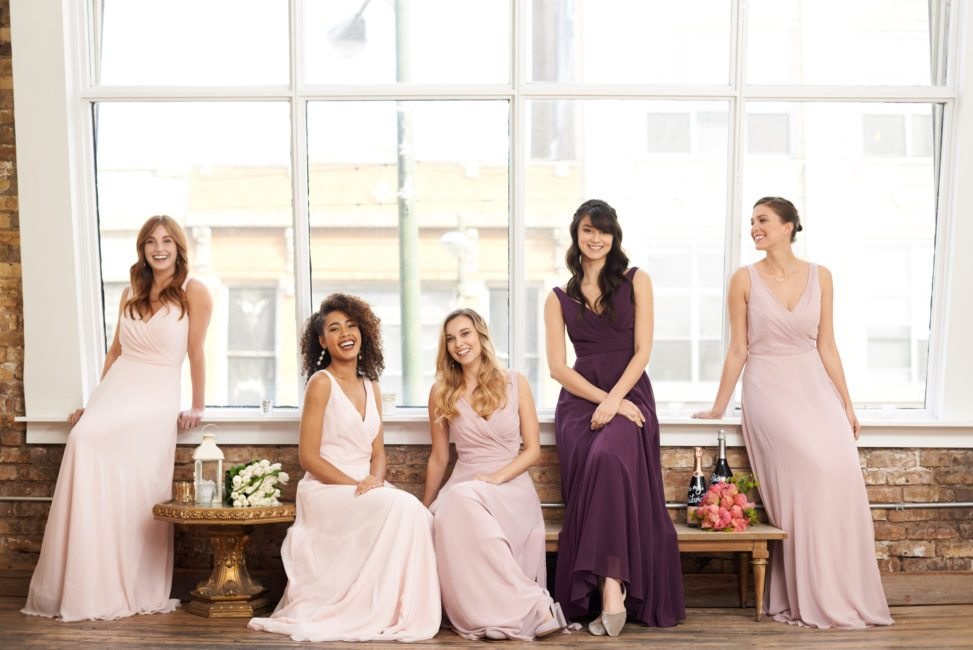 bridesmaids in pink or purple floor-length dresses, sitting in front of a brightly lit loft window
