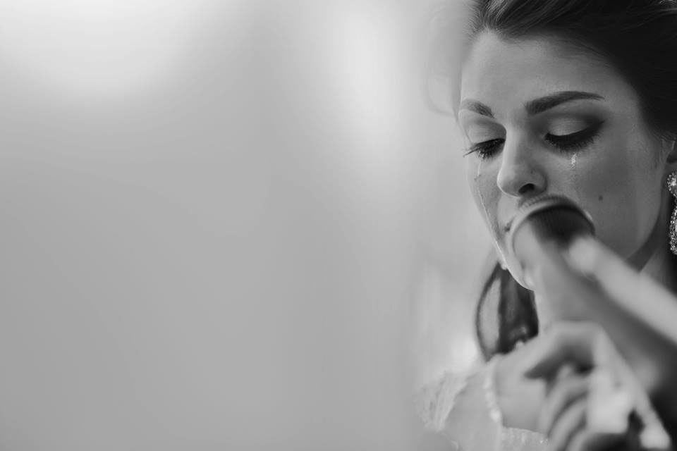 bride at microphone with single tear rolling down her cheek