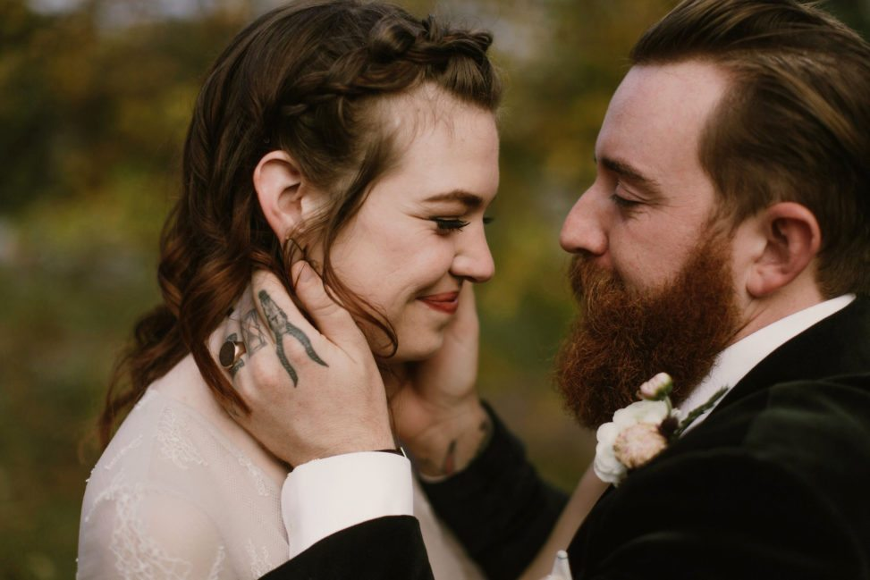 groom with tattooed hands holding bride's face