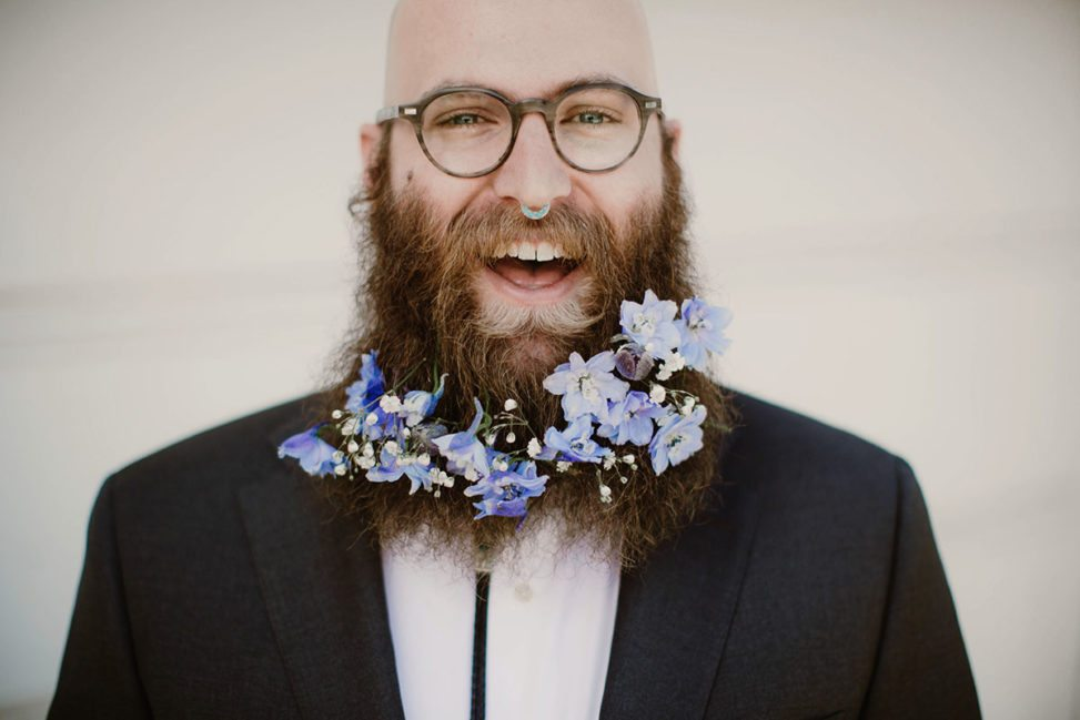 bald man with nose ring and beard with flowers
