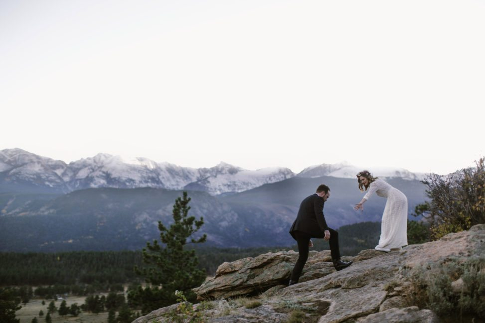 bride and groom climbing rocks in front of white mountain peaks