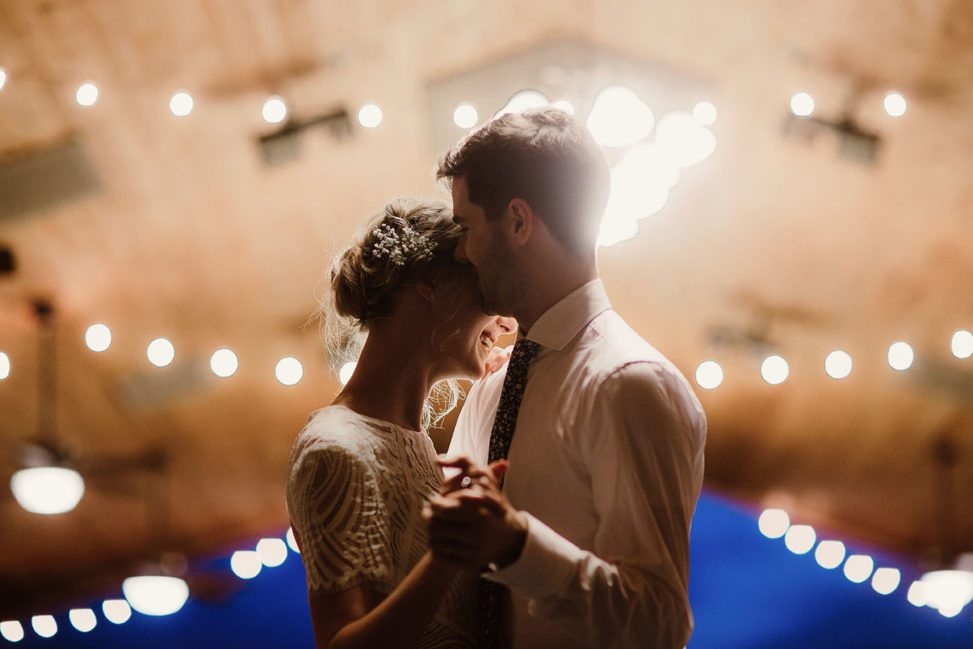 bride and groom dancing in a barn with string lights