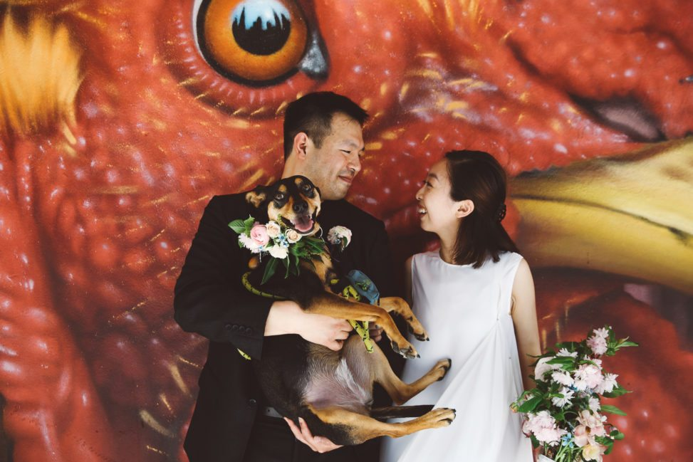 Couple smiles at each other in front of a giant mural of a red bird with yellow beak, the skyline reflected in its pupil. The groom holds a dog with a flower wreath collar; the bride holds a corresponding bouquet.