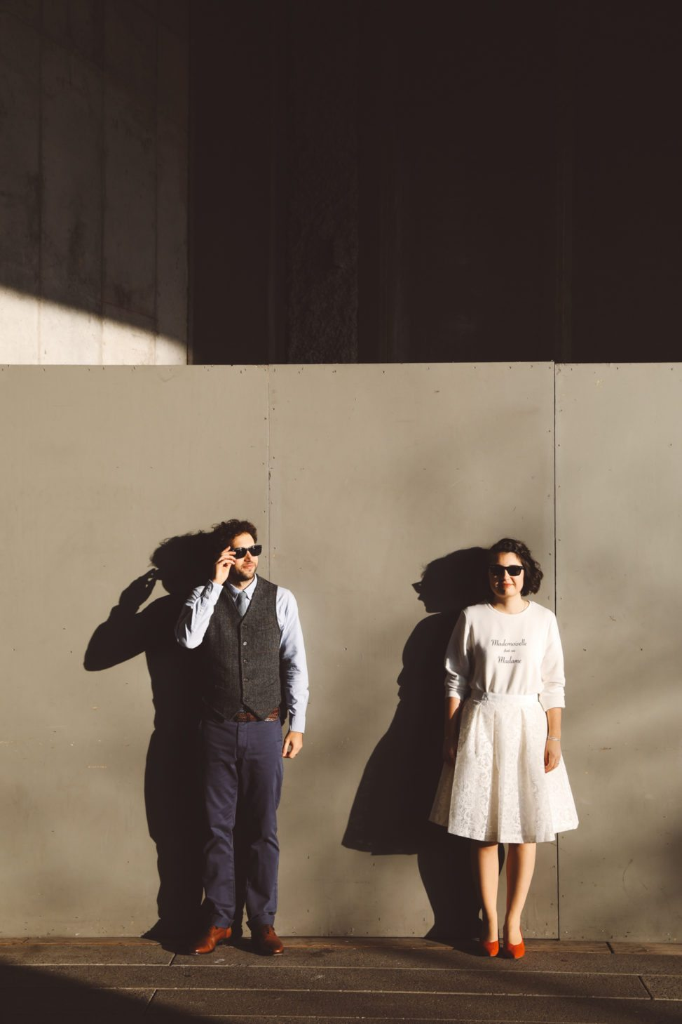 Couple in sunglasses stand in front of a temporary wall outside, the sun creating dramatic elongated shadows on the wall behind them
