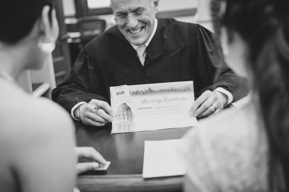Two women sitting in front of a clerk being presented their marriage license
