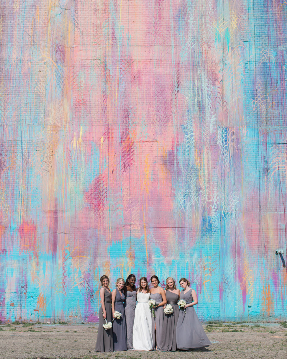 a bride and her bridal party stand together with a large abstract mural backdrop