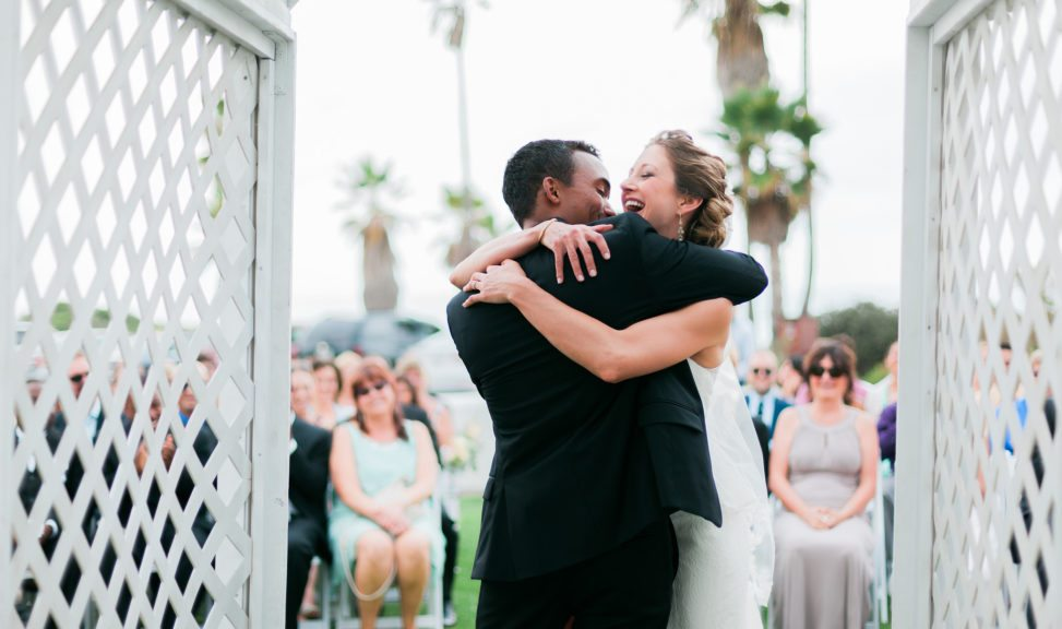 A wedding couple embrace and laugh at the end of their ceremony
