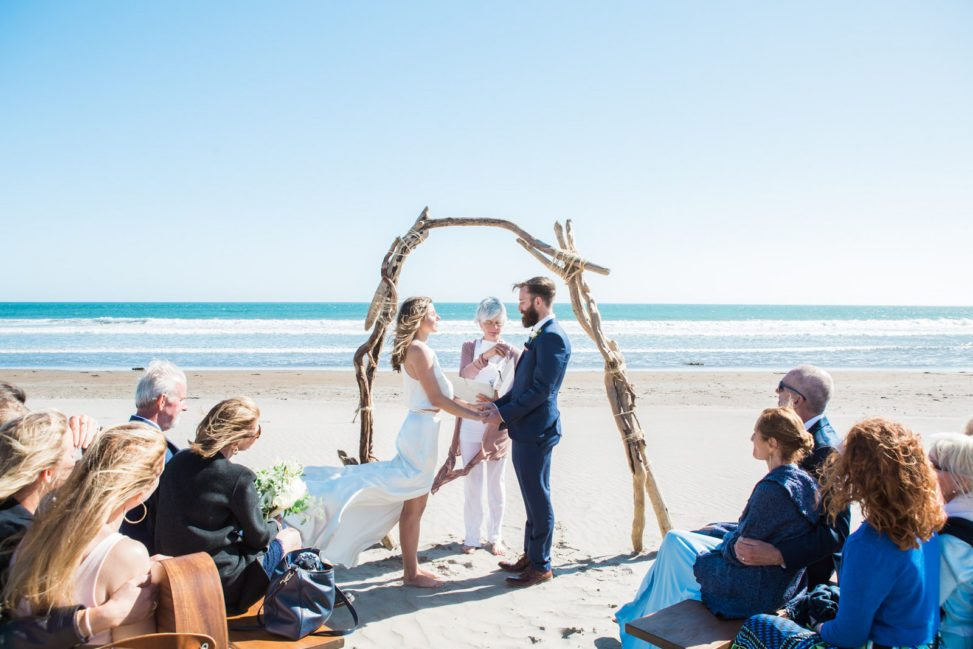wedding ceremony at a windy beach with a driftwood arch