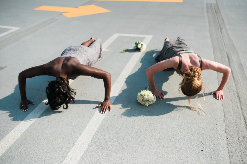a bride and bridesmaid doing pushups in a parking lot