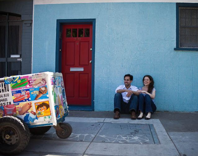 woman and her husband sitting in front of a light blue tiled wall next to an ice cream push cart