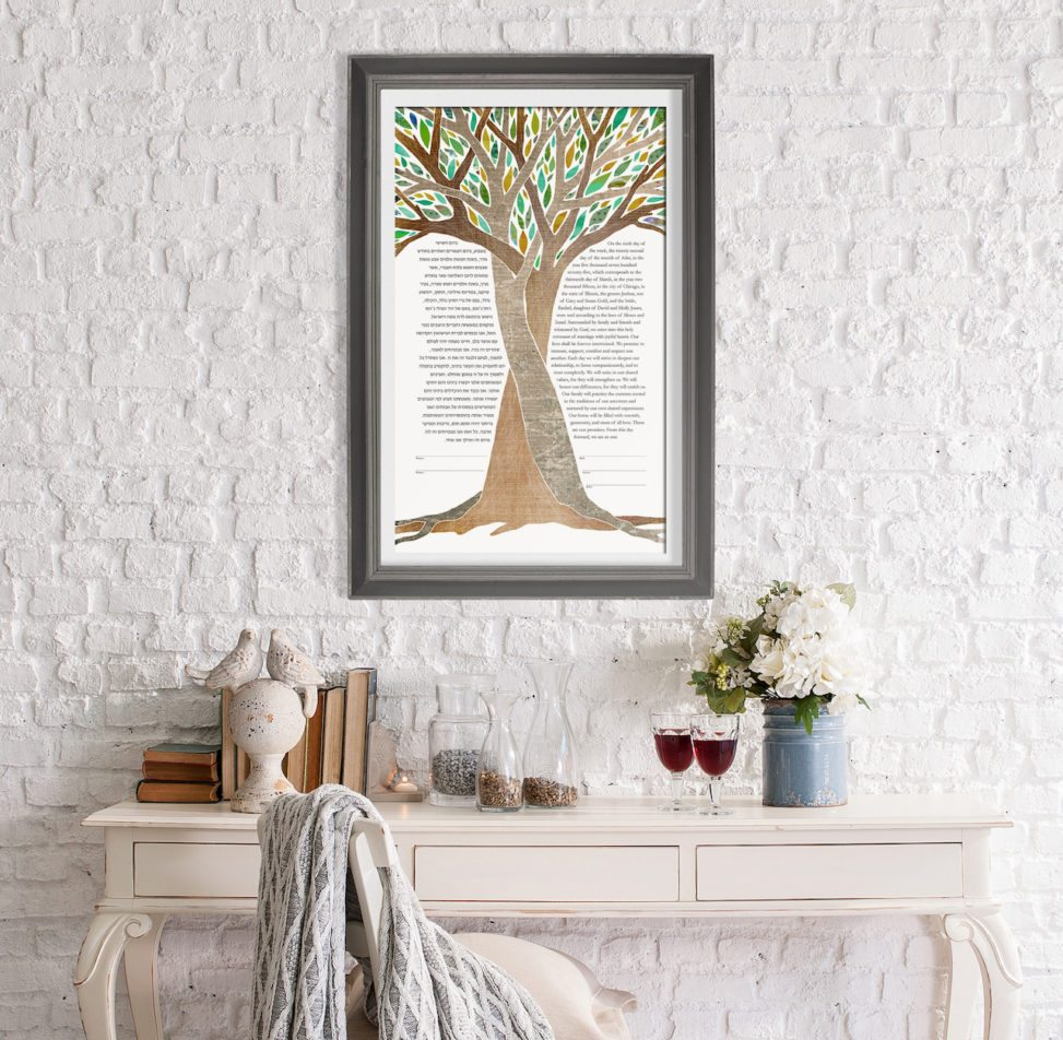 a ketubah featuring an illustration of intertwined trees hanging on a wall above a desk