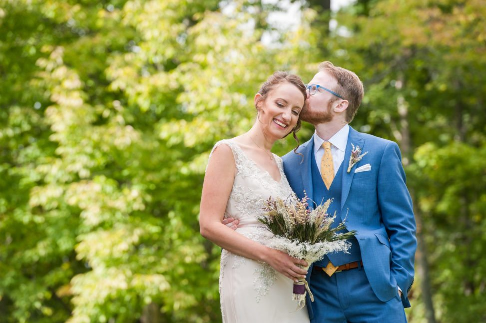 groom in blue suit with blue glasses kissing bride's temple in front of green trees
