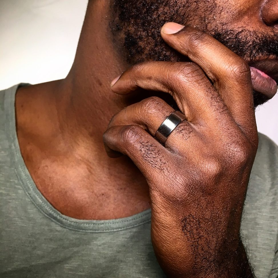 closeup of a man holding his chin, showing his ring