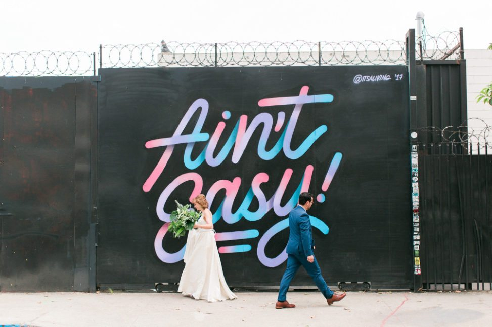 couple in wedding dress and suit in front of mural that says ain't easy
