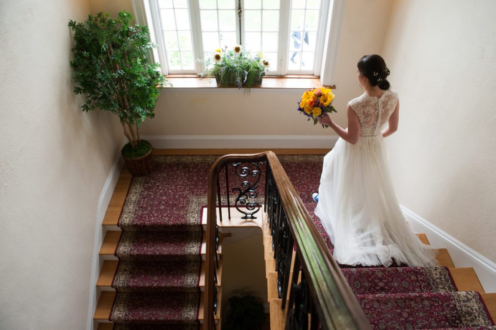 a bride walks down a staircase holding her bouquet