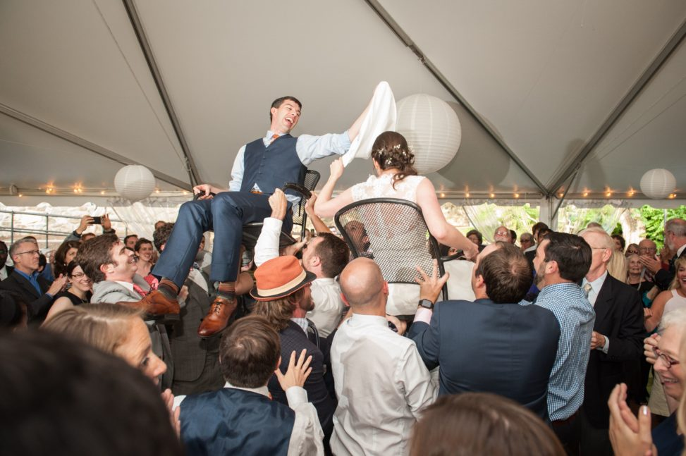 bride and groom lifted on chairs during horah