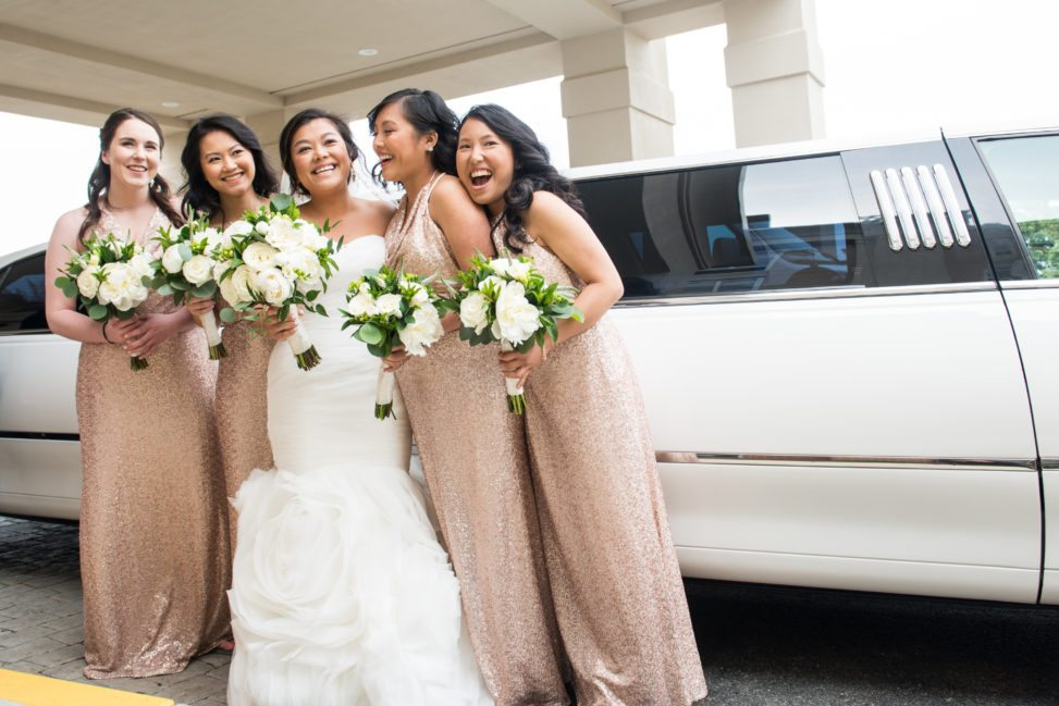 bride with four bridesmaids in pink sequined dresses in front of white limo