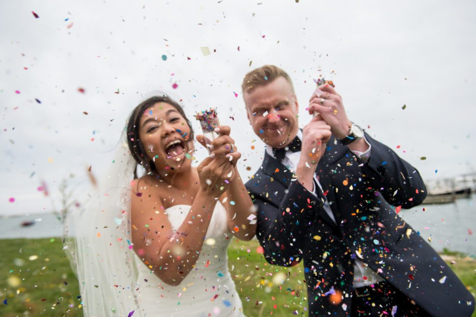bride and groom shooting confetti poppers and laughing