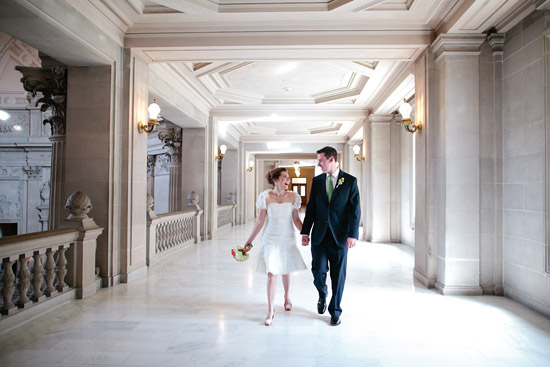 couple holding hands and walking down hallway at San Francisco City Hall