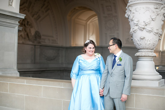 woman in blue wedding dress holds hand of man in grey suit at San Francisco City Hall