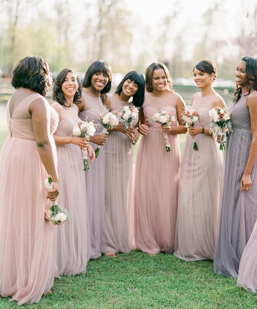 bridesmaids wearing mismatched bridesmaid dresses in a combination of light purple and mauve and blush