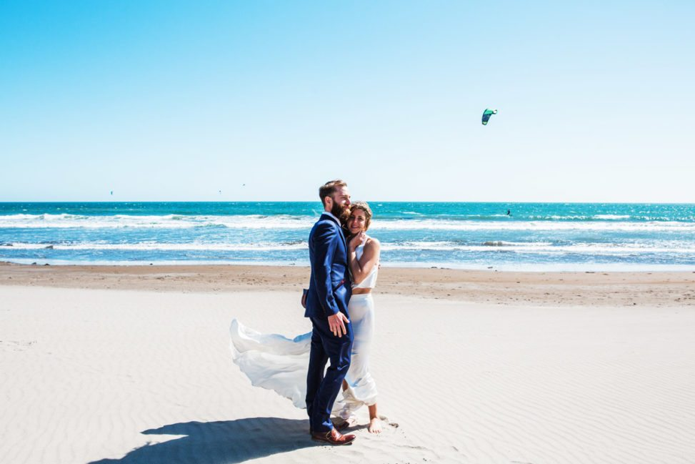 waves at a sunny beach with a happy couple standing around