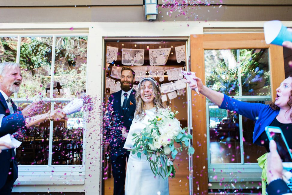 a smiling couple walking through a door being showered with confetti
