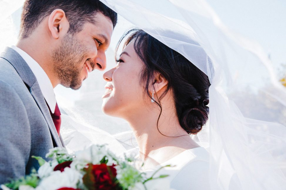 a woman and man underneath a veil, smiling