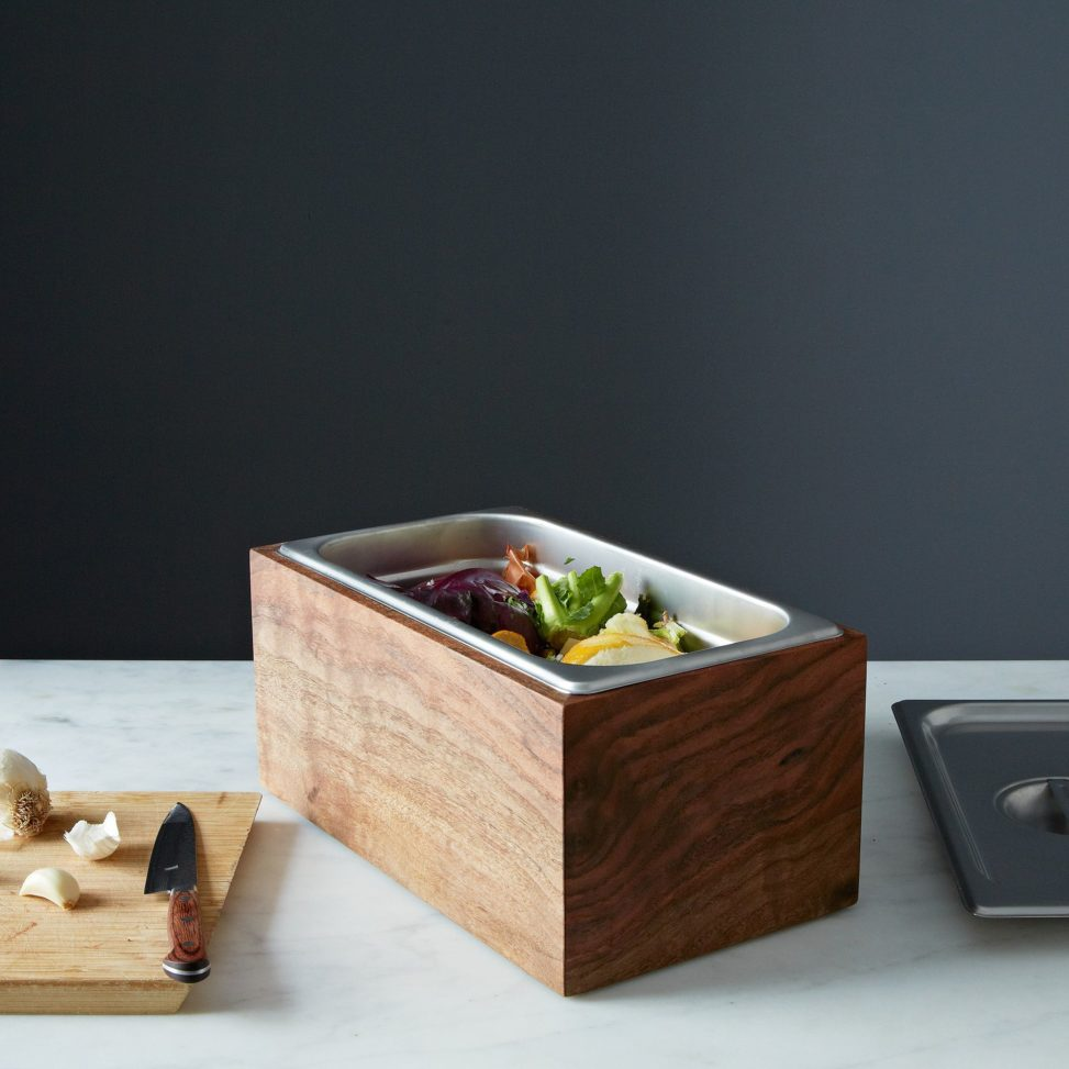 walnut and metal compost bin with vegetables inside on counter