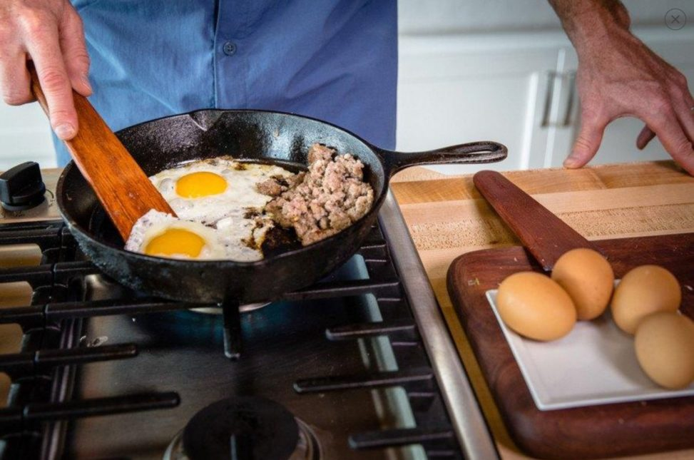 Person sauteing eggs on stove with wooden tools