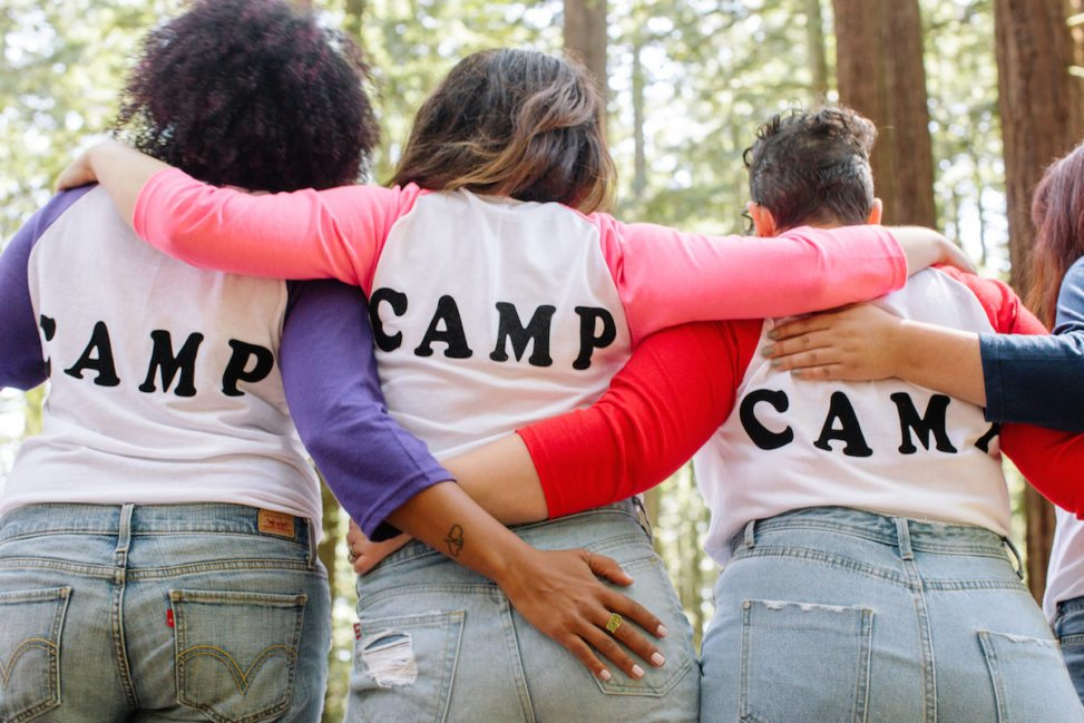 women wearing Camp tees in the woods, with their arms around eachother