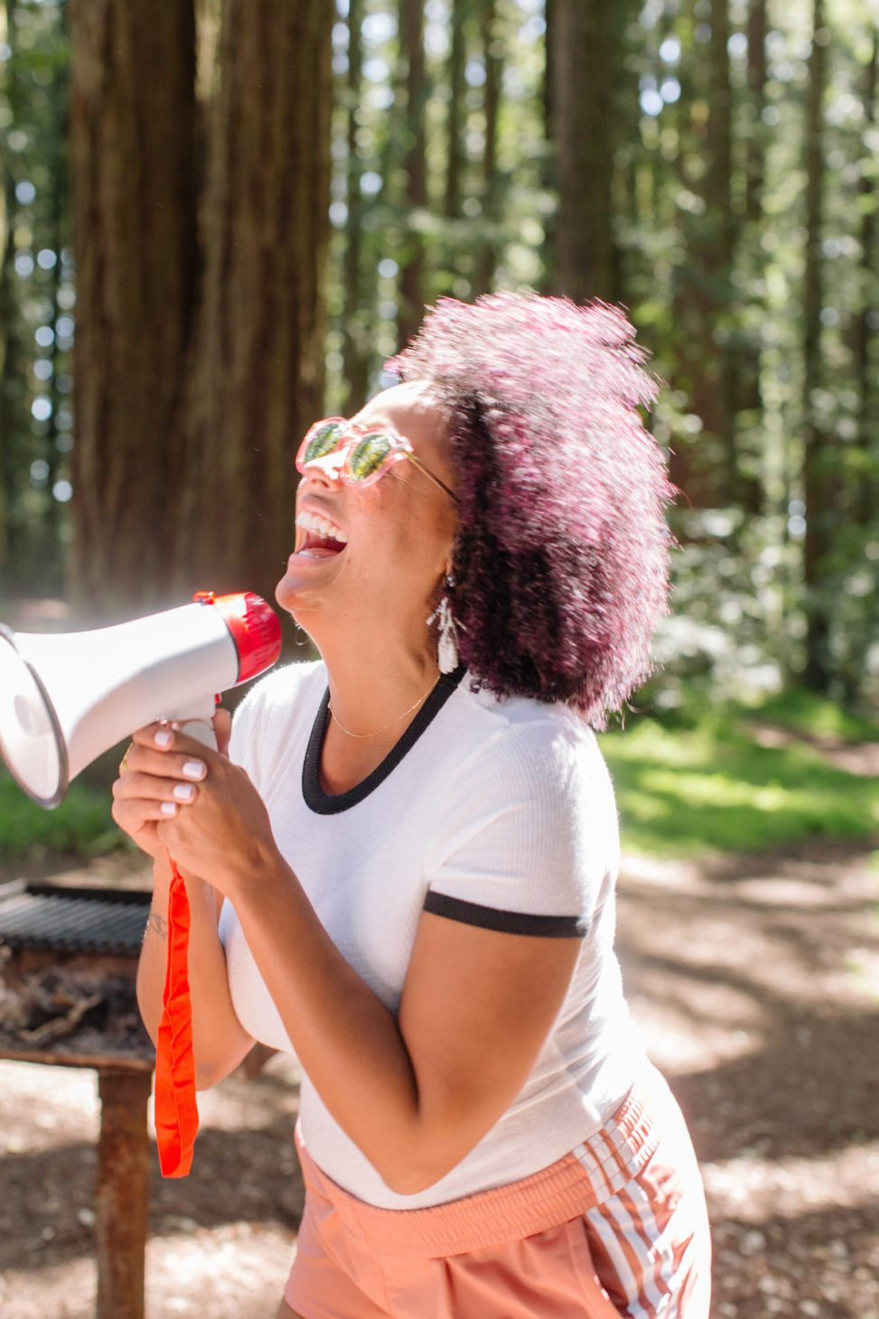 woman in the woods near a grill holding a megaphone and laughing