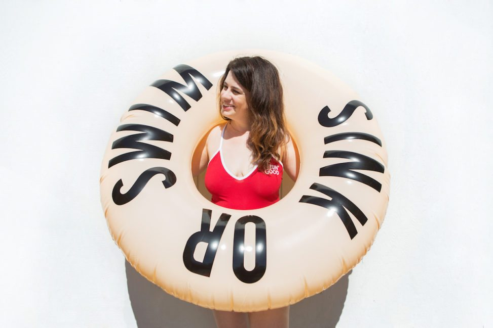 "woman in red swimsuit holding an inner tube that reads ""Sink or Swim"""