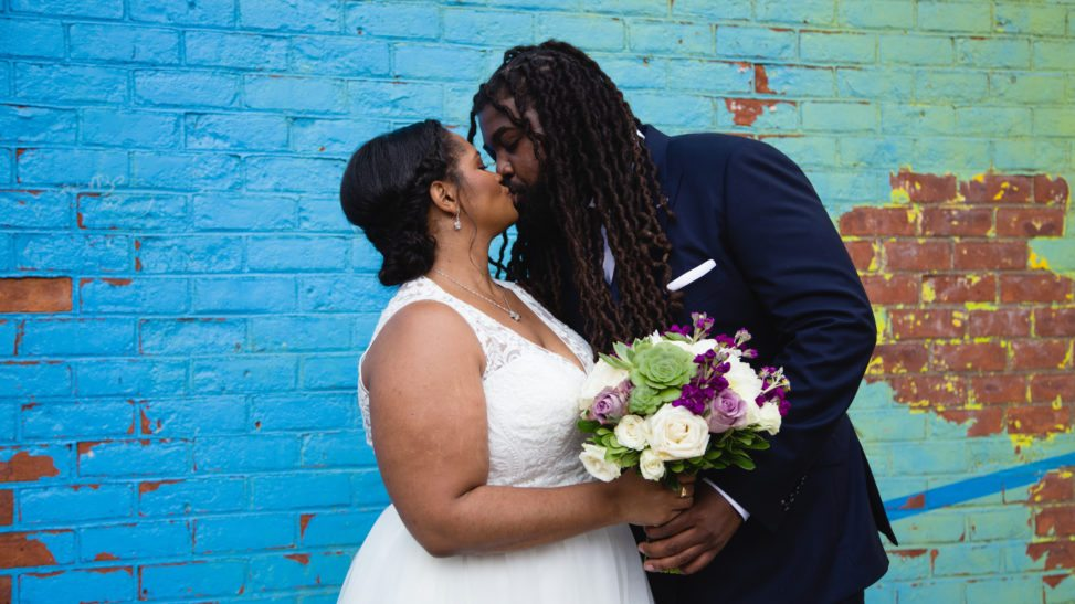 a wedding couple kiss in front of a colorful wall