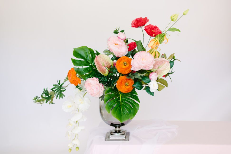 Fake flower arrangement that looks real with silk tropical leaves and silk peonies