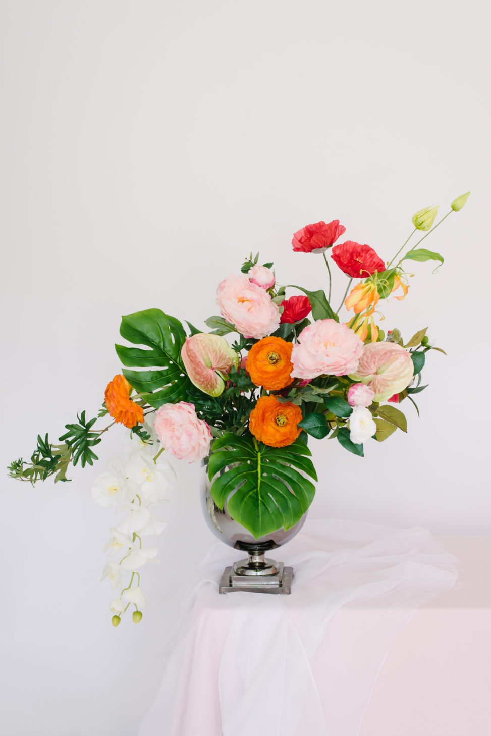 vase with fake floral red, pink, and orange bouquet that looks real on white background