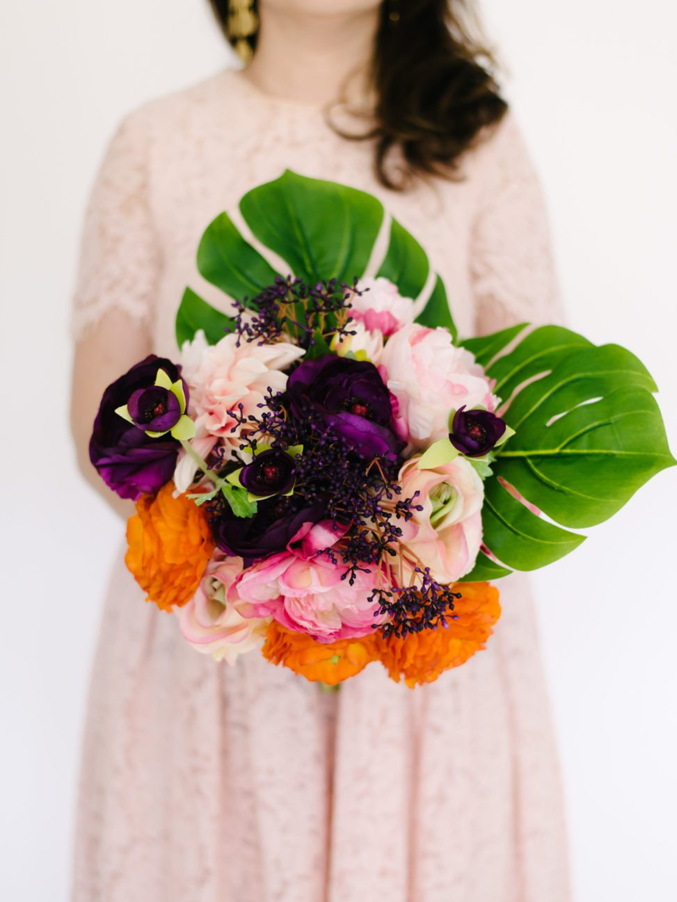 Fake flower arrangement that looks real with silk leafs and silk peonies held by woman in dress