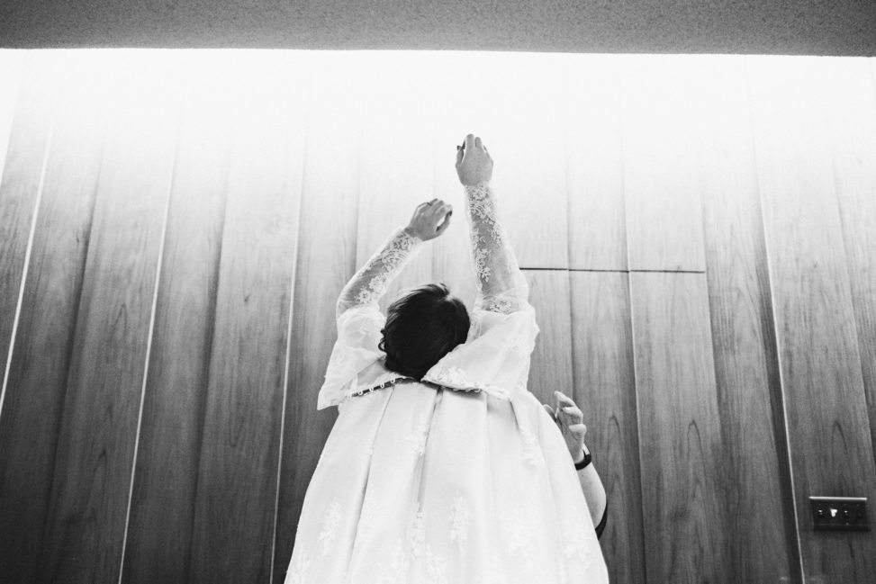 a woman puts on her wedding dress