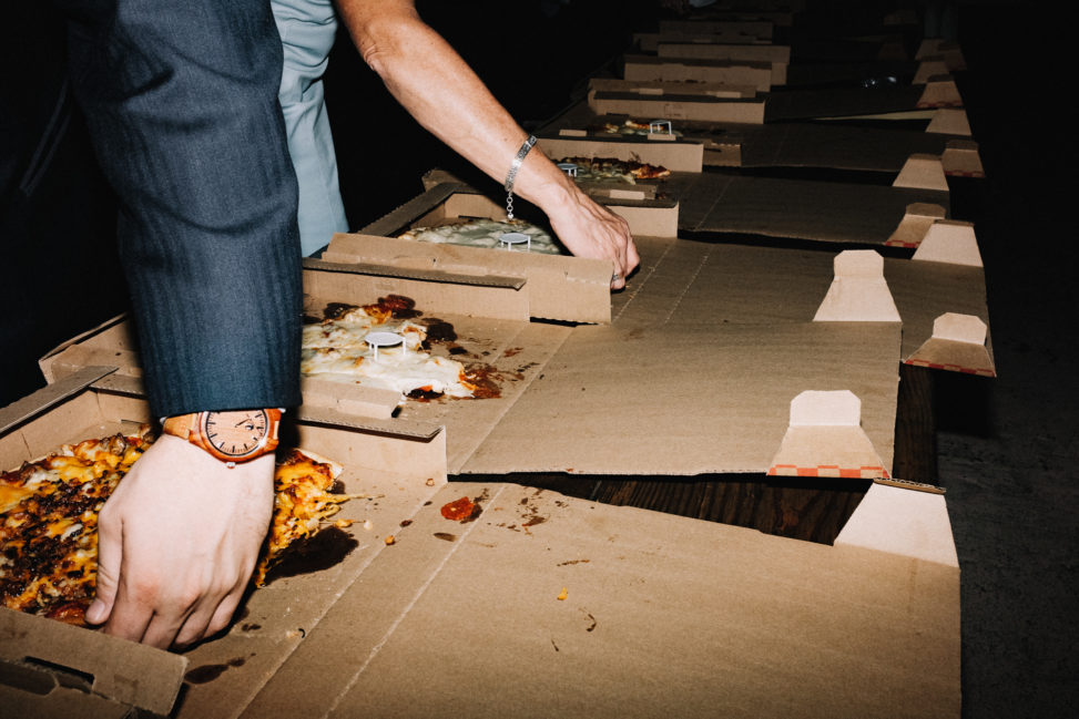 a row of pizzas in boxes during a wedding reception